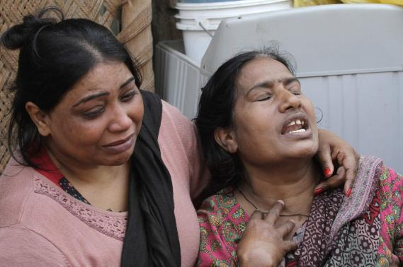 Women mourn the death of their relative who was killed in a suicide attack on a church in Lahore