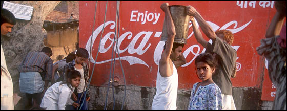 Poor people fetching water from a communal well emblazoned with Coca Cola advertisement.